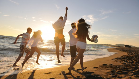 happy young people group have fun white running and jumping on beacz at sunset time